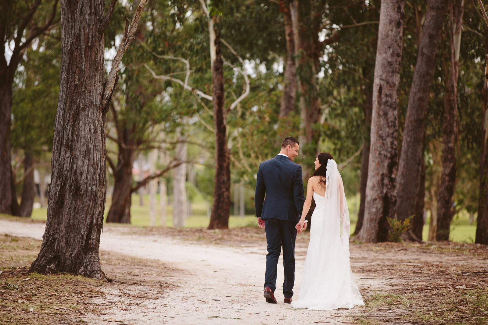 bride and groom walking a path at Parkwood International golf course